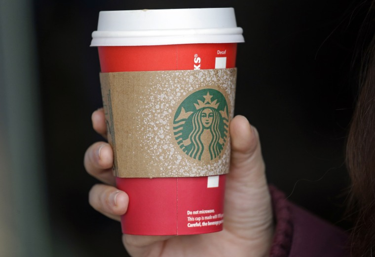 A customer carries a coffee drink in a red paper cup, with a cardboard cover attached, outside a Starbucks coffee shop in the Pike Place Market, Tuesday, Nov. 10, 2015, in Seattle.