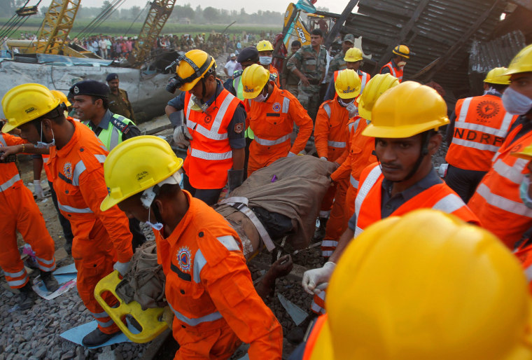 Image: Rescue workers remove the remains of a passenger from the site of a train derailment in Pukhrayan, south of Kanpur city, India