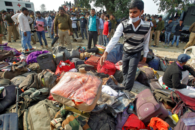 Image: A man sorts through luggage at the site of a train derailment in Pukhrayan, south of Kanpur city, India