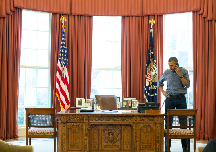 Image: President Barack Obama talks on the phone in the Oval Office with Russian President Vladimir Putin
