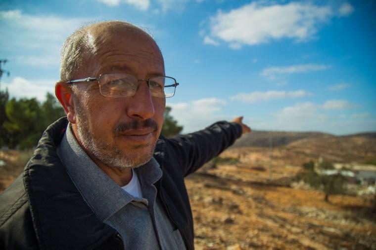 Image: Ibrahim Yacoub, points to DzAmonadz, the Israeli settlement