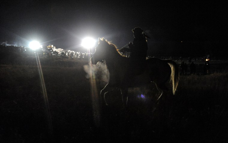 Image: A horse gallops through a confrontation between police and protesters during a protest against plans to pass the Dakota Access pipeline near the Standing Rock Indian Reservation, near Cannon Ball, North Dakota, U.S.