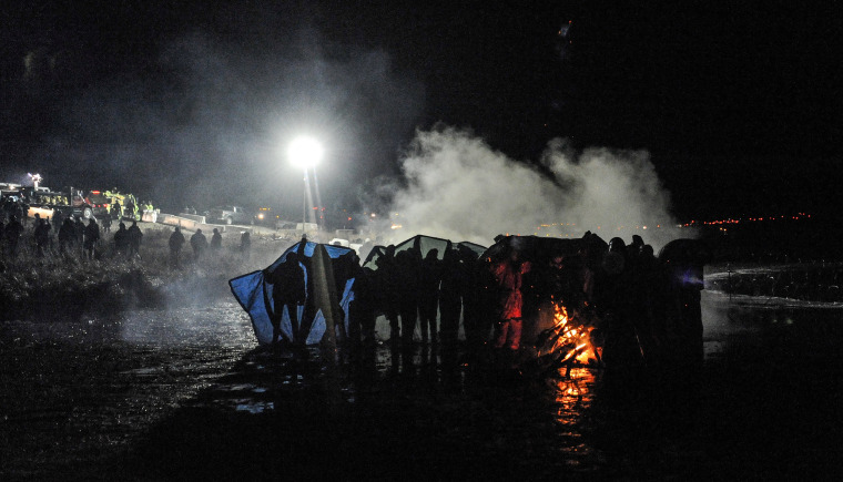 Image: Police use a water cannon to put out a fire started by protesters during a protest against plans to pass the Dakota Access pipeline near the Standing Rock Indian Reservation, near Cannon Ball, North Dakota, U.S.