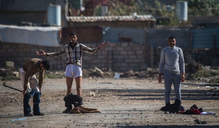 Image: Iraqi men drop their pants before being allowed to approach a position held by the Iraqi Special Forces' second division in Mosul's eastern district of Karkukli