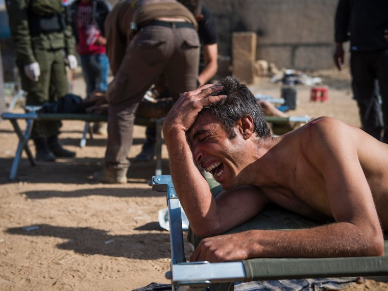 Image: Mosul resident Hassan suffering shrapnel wounds to his upper body cries out for his son