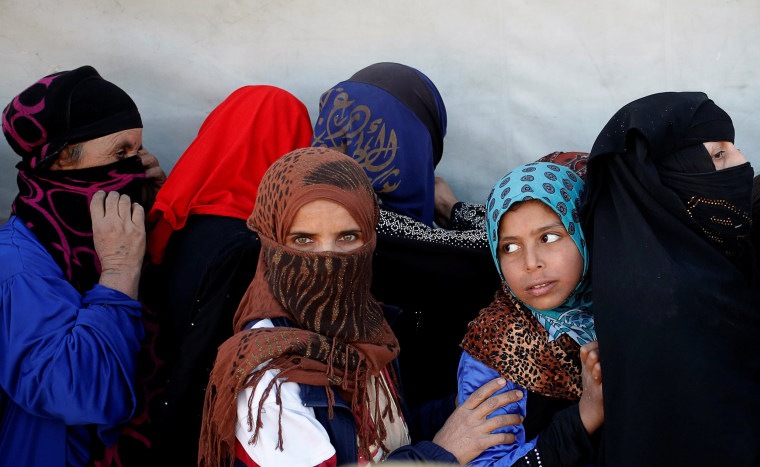 Image: Women wait for food donated by an Iraqi government organisation at the outskirts of Mosul