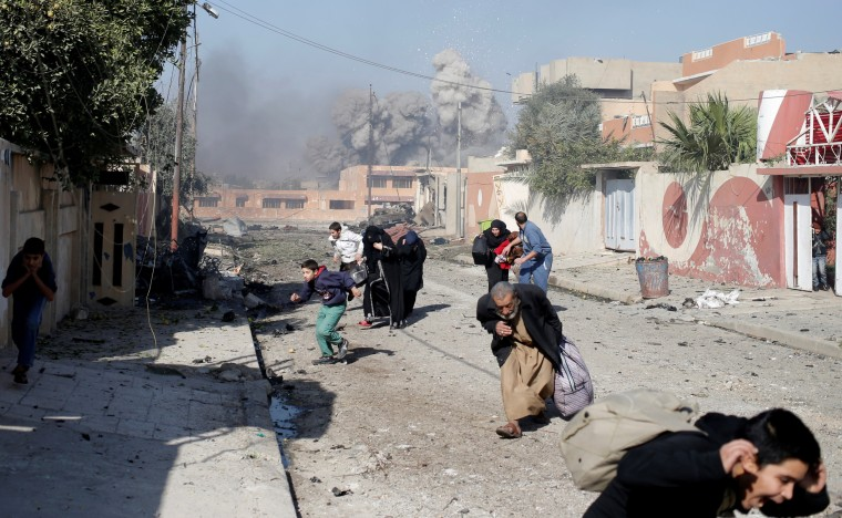 Image: People run in panic after a coalition airstrike hit Islamic State fighters positions in Tahrir neighbourhood of Mosul