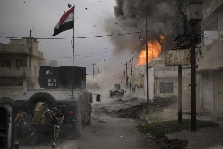 Image: A car bomb explodes next to Iraqi Special Forces armored vehicles as they advance towards Islamic State held territory in Mosul, Iraq
