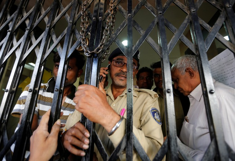 Image: A policeman closes the gate from inside as people try to enter a bank in Ahmedabad
