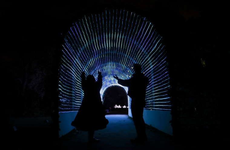 Image: Models pose for a photograph in a tunnel of lights at Kew Gardens in west London