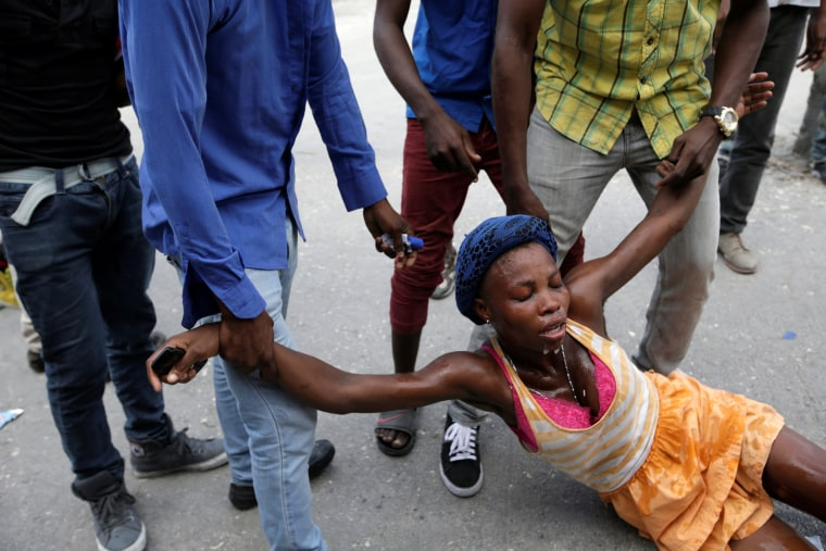 Image: Men help a woman affected by tear gas used by National Police officers to disperse a demonstration of supporters of Fanmi Lavalas political party in the streets of Port-au-Prince, Haiti