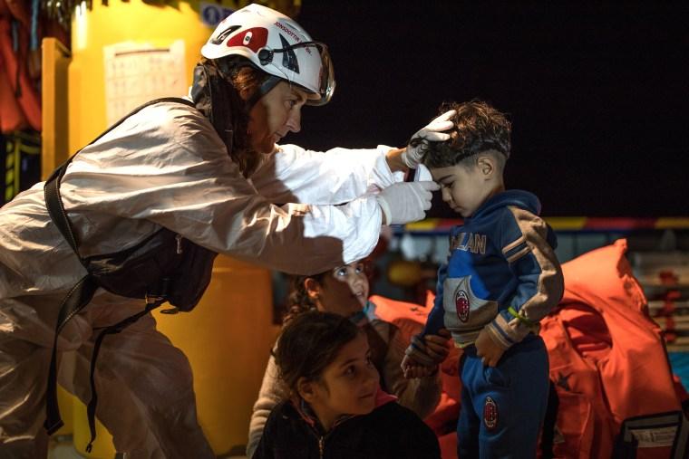 Refugee children have their temperatures taken after being rescued.