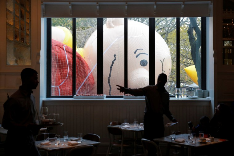 Image: Wait staff work in the Storico restaurant beside the inflated Charlie Brown balloon ahead of the 90th Macy's Thanksgiving Day Parade in Manhattan, New York, U.S.