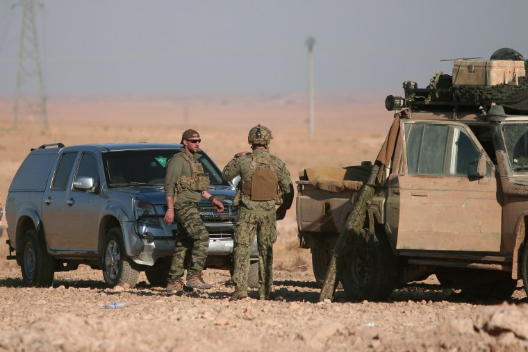 Image: U.S. fighters stand near military vehicles, north of Raqqa city