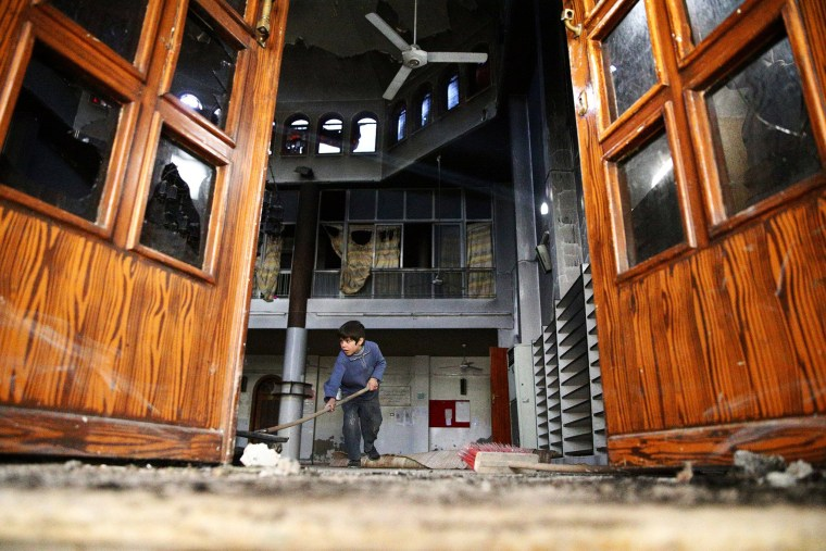 Image: A boy cleans a damaged mosque at a site hit yesterday by an airstrike in the rebel held besieged Douma neighbourhood of Damascus