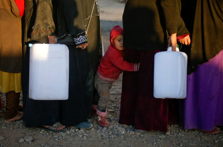 Image: Displaced Iraqis, who fled the Islamic State stronghold of Mosul, carry empty containers as they wait in line to fill them with fuel to be used for cooking and lighting at Khazer camp