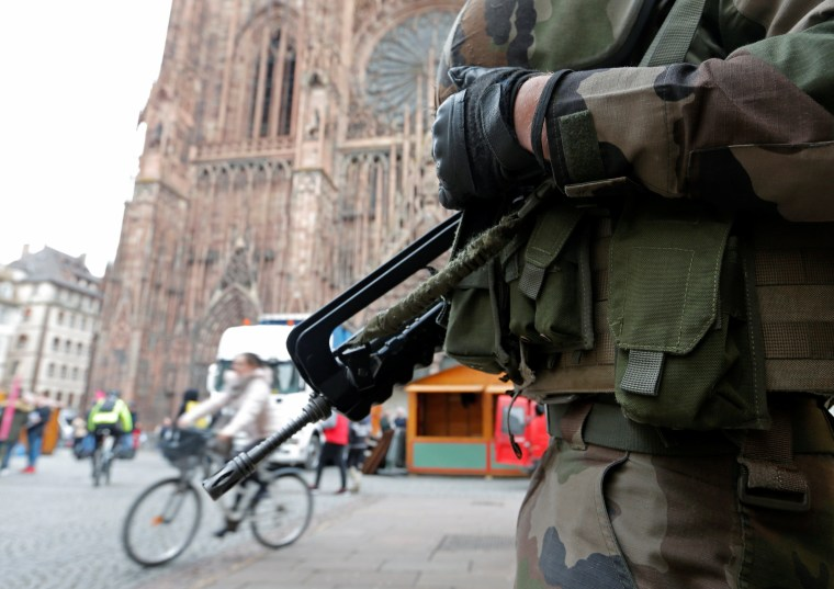 Image: A French soldier stands guard near Strasbourg's cathedral