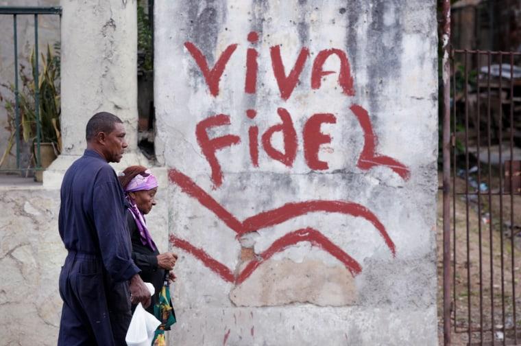 """Image: People walk past a graffiti that reads \""""Long live Fidel\"""" in Havana, Cuba"""