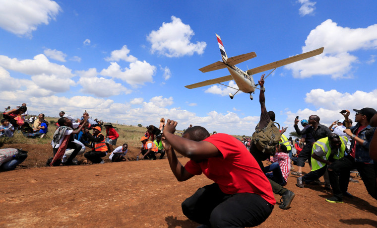 Image: Spectators react as a plane flies over them during the Vintage Air Rally at the Nairobi national park in Kenya's capital Nairobi