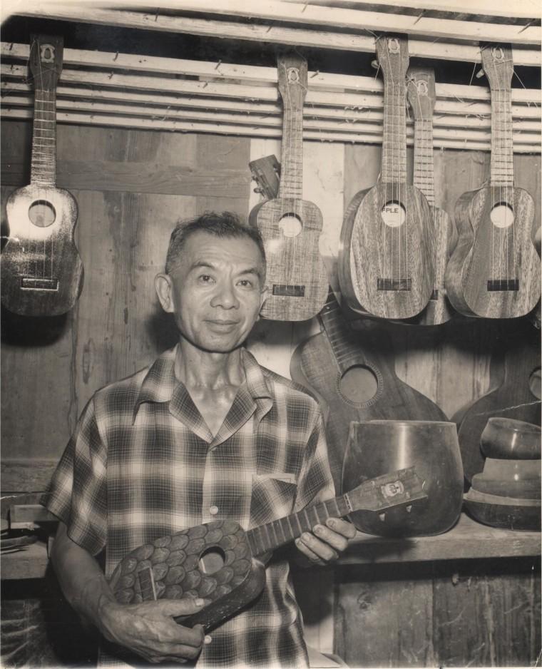 Samuel Kamaka Sr holding a pineapple ukulele.