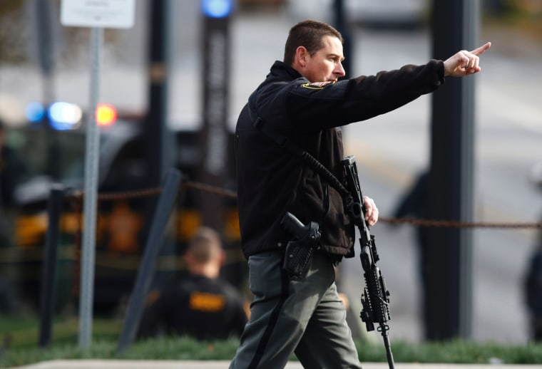 Image: A law enforcement official motions for people to leave the area outside of a parking garage on the campus of Ohio State University as they respond to an active attack in Columbus, Ohio