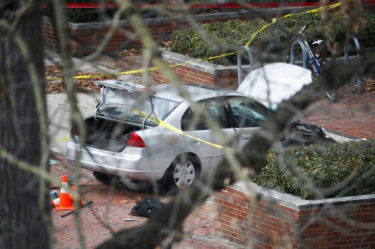 Image: A car inside a police line sits on the sidewalk as authorities respond to an attack on campus at Ohio State University