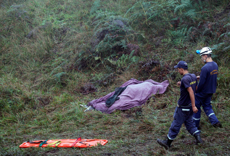 Image: Rescue workers walk next to a body from a plane that crashed into Colombian jungle with Brazilian soccer team Chapecoense near Medellin