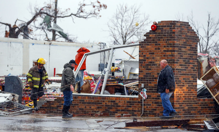 Image: A Rosalie firefighter helps remove debris from the Rosalie Plaza after a tornado ripped through the town