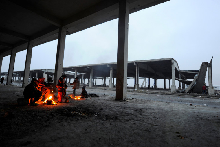Image: Syrians evacuated from eastern Aleppo keep warm by a fire, under a shelter in government controlled Jibreen area in Aleppo