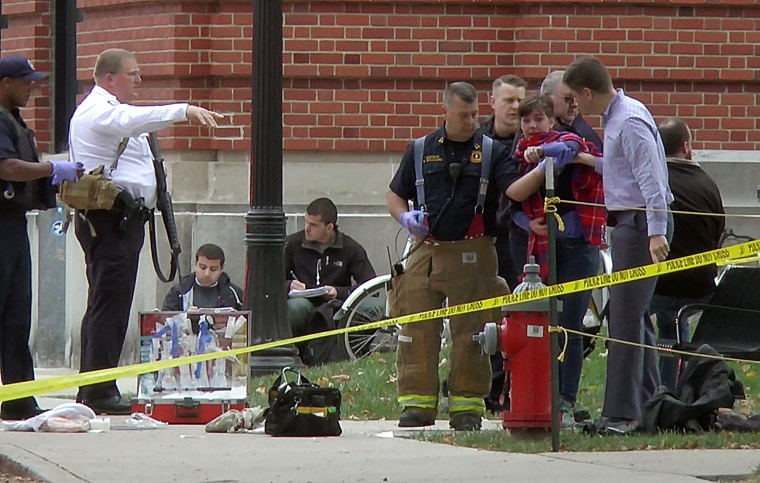Image: A girl is led to an ambulance by emergency personnel following an attack at Ohio State University's campus in Columbus