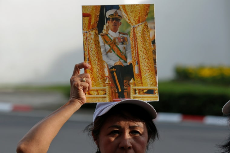 Image: A woman holds up a picture of Thailand's Crown Prince Maha Vajiralongkorn
