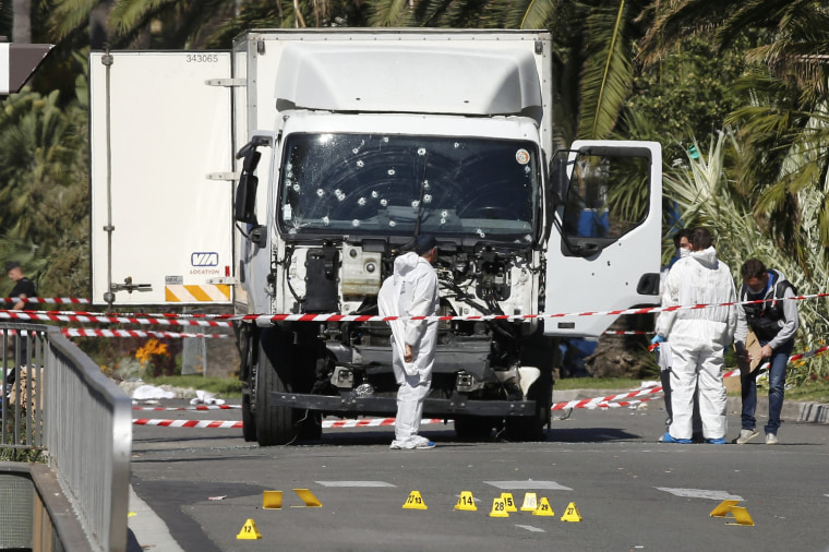 Image: Investigators continue to work at the scene near the heavy truck that ran into a crowd at high speed killing scores who were celebrating the Bastille Day July 14 national holiday on the Promenade des Anglais in Nice