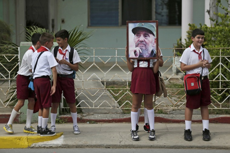 Image: Children stand along a street while waiting for the ashes of Fidel Castro to pass in Cardenas