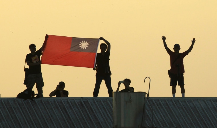 Locals on a warehouse rooftop display the national flag while watching Taiwan fighter jets practice emergency landing drills on a closed section of highway during the annual Han Kuang military exercises in  2014, in Chiayi, central Taiwan.