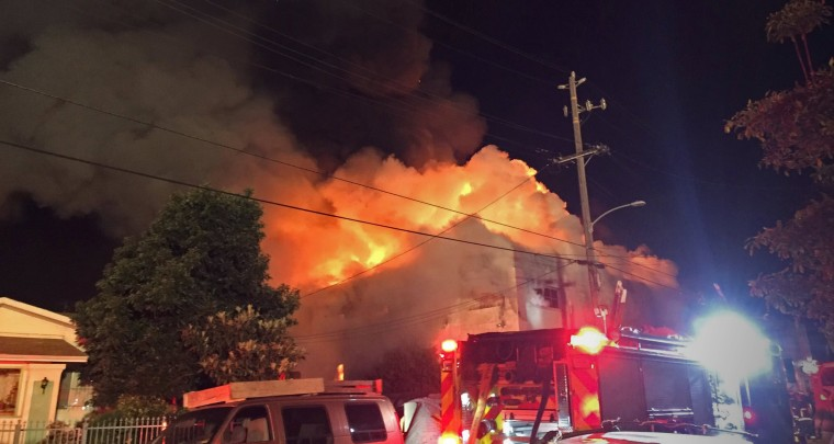 Image: Flames rise from the top of a warehouse, which caught fire during a dance party in Oakland