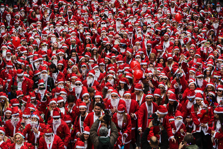 """Image: Runners dressed as Santa Claus take part in the 3rd edition of the \""""Athens Santa Claus Run\"""" in central Athens"""