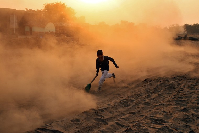Image: A boy plays with a makeshift wheel outside his house on a dusty road in Jammu