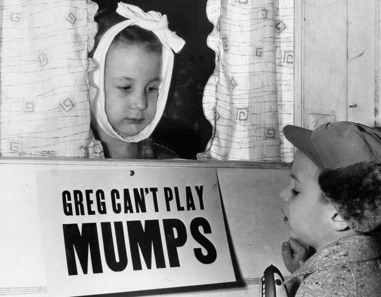 A 1957 photo shows Greg Cox, left, 7, in Altamont, Ill., as he looks at his friend Jon Douglas, 6, through the doorway while he recovers from mumps.