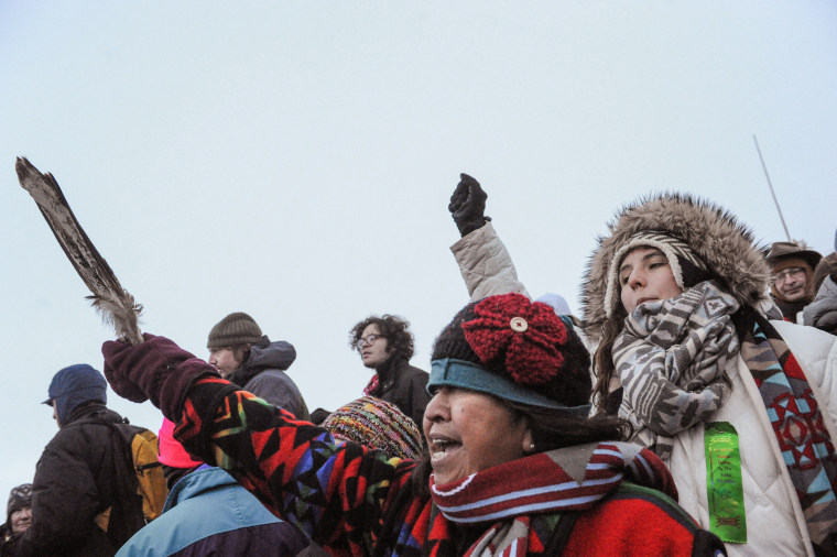 "Image: A woman from the Tlingit Tsimphean tribe holds an eagle feather into the air in Oceti Sakowin camp as ""water protectors"" continue to demonstrate against plans to pass the Dakota Access pipeline near the Standing Rock Indian Reservation, near Cannon"