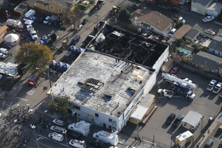 Image: Firefighters work inside the burned warehouse following the fatal fire in the Fruitvale district of Oakland