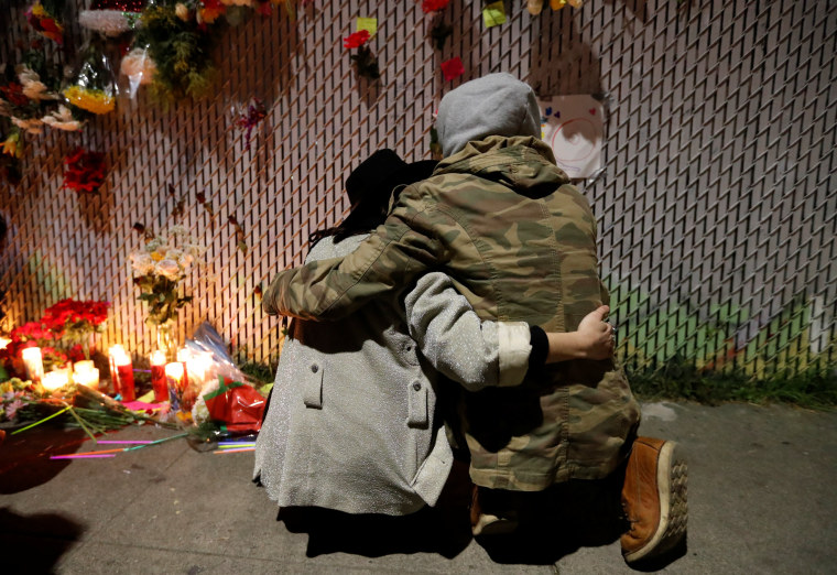 Image: Rachel Saxer embraces La Tron at a makeshift memorial near the scene of a fatal warehouse fire in the Fruitvale district of Oakland, California