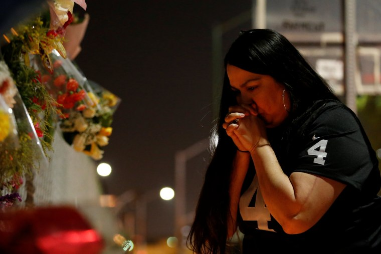 Image: A woman prays at the makeshift memorial near the scene of a fatal warehouse fire in the Fruitvale district of Oakland, California