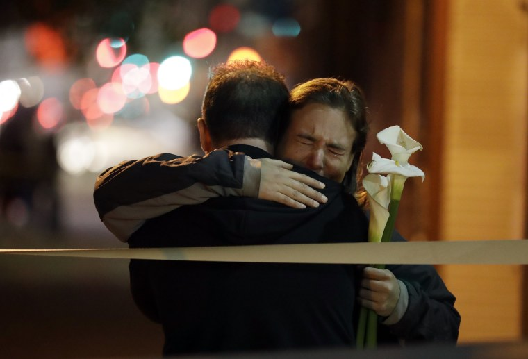 Image: Mourners embrace near the site of a warehouse fire
