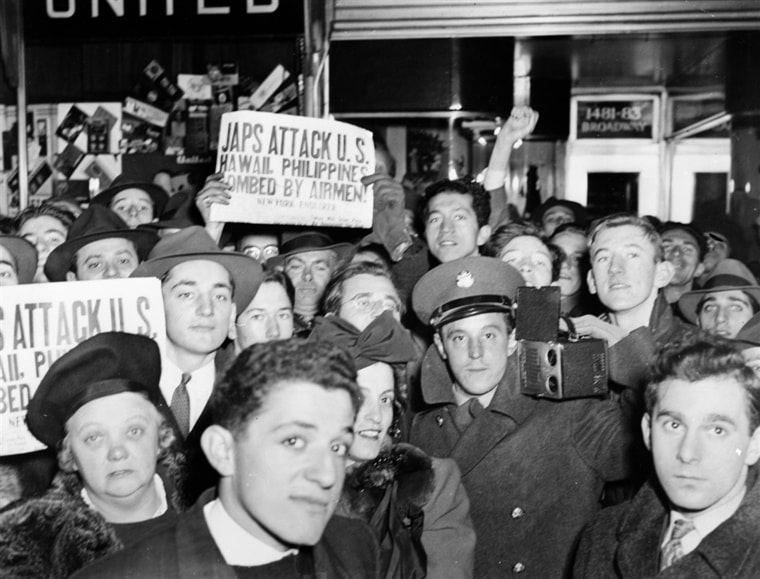 Image: A crowd on Broadway in New York City hold up newspapers announcing the Japanese attack on Pearl Harbor.