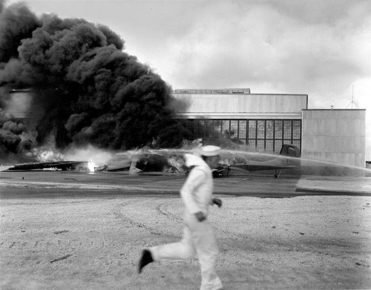 Image: A sailor runs for cover past flaming wreckage hit by dive bombers that had already blasted Pearl Harbor and Hickam Field.