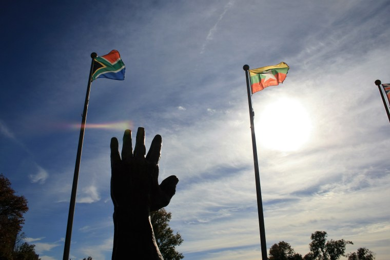 The Myanmar flag flies on the right next to a statue at Oral Roberts University in Tulsa, Oklahoma.