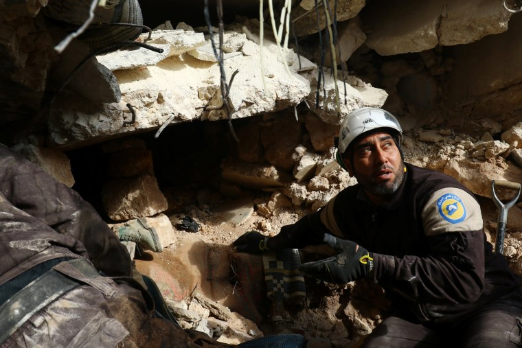 Image: Civil Defence members look for survivors under rubble of damaged buildings after air strikes on the northern neighbourhood of Idlib city