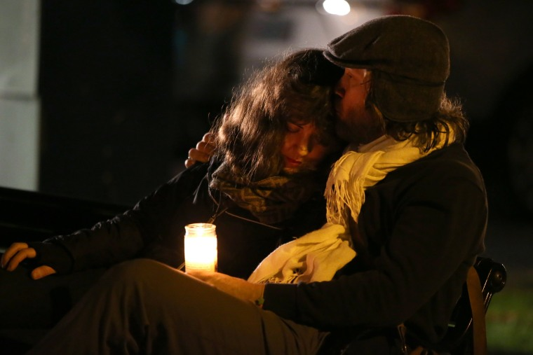 Image: People attend a vigil for the victims of the fatal warehouse fire in Oakland