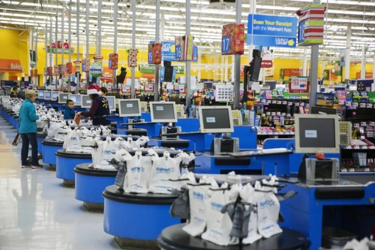 Employees work at the checkout counters of a Walmart store in Secaucus, New Jersey