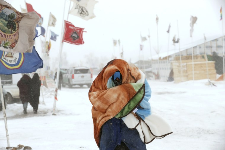 Image: A camper braces against high winds and a blizzard while walking inside of the Oceti Sakowin camp adjacent to the Standing Rock Indian Reservation, near Cannon Ball